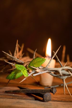 Easter image of a crown of thorns, a candle and green leaf of Hope photo