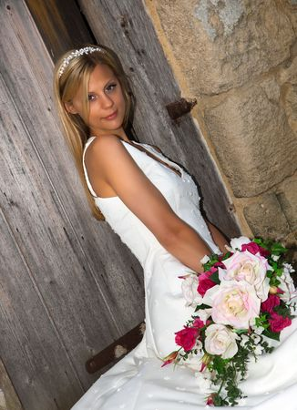 Young blonde bride in white against a grunge medieval barn wall Stock Photo - 6250499