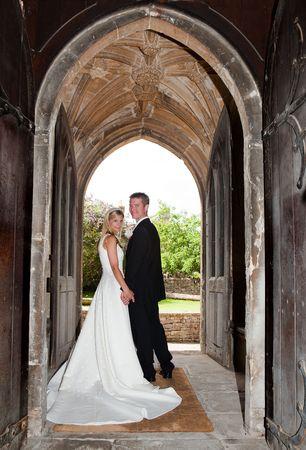 recien casados: Par de boda j�venes posando en una entrada de iglesia medieval inglesa