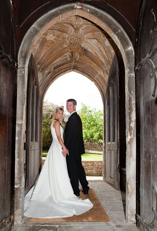 married together: Young wedding couple posing in an English medieval church entrance Stock Photo