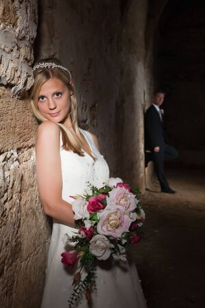 Bride in white posing against a medieval grunge barn wall Stock Photo - 6250501