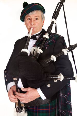 scot: Scottish highlander wearing kilt and playing bagpipes Stock Photo