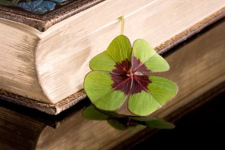 buena suerte: Libro de suerte con un tr�bol de cuatro hojas, sirviendo como un marcador de libro  Foto de archivo