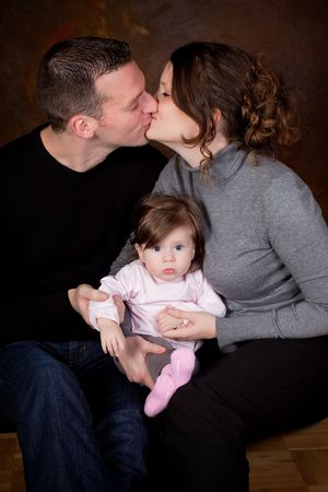 Happy mother and father kissing eachother holding their 4 months old baby photo