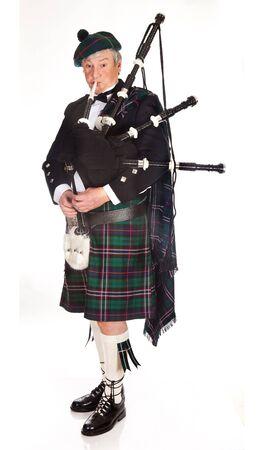 gaita: Montañés escocés vistiendo kilt y tocando la gaita Foto de archivo