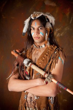 navajo: Portrait of an Indian in traditional costume wearing eagle feathers, coyote fur and beads