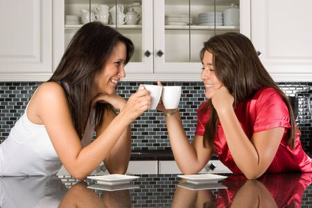 coffee houses: Two young women having a coffee break in the kitchen