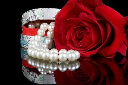 Little box filled with a pearl necklace and a perfect red rose photo
