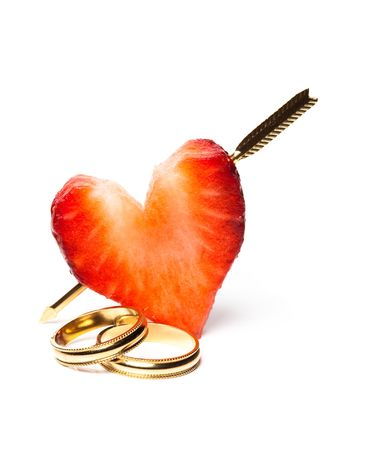 Strawberry pierced by cupids arrow, and wedding rings photo