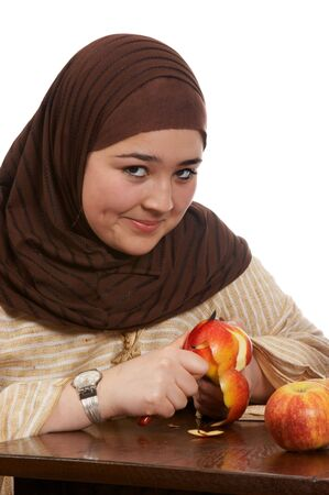 purdah: Young veiled woman peeling an apple with a smile Stock Photo