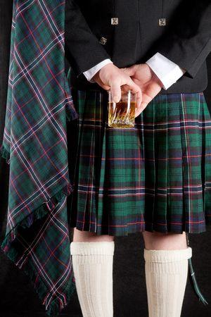 highlander: Scotsman tenendo che il bicchiere di whisky dietro � kilt