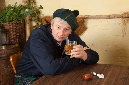 scot: Funny scotsman wearing kilt drinking a glass of whisky in a pub