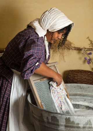 Victorian woman washing laundry with an antique washboard photo