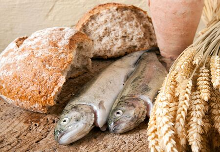 Wine jug, bread and fish as symbols of christian religion photo