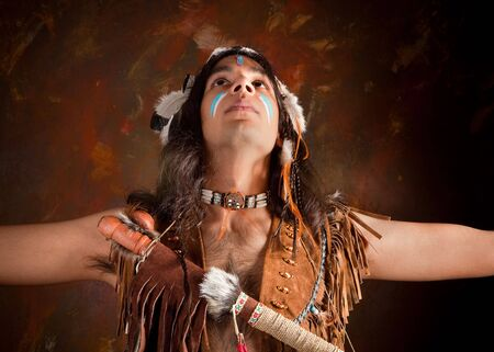 warrior tribal: Portrait of an Indian in traditional costume wearing eagle feathers, coyote fur and beads