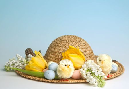 Straw hat decorated for easter with flowers, chicks and easter eggs