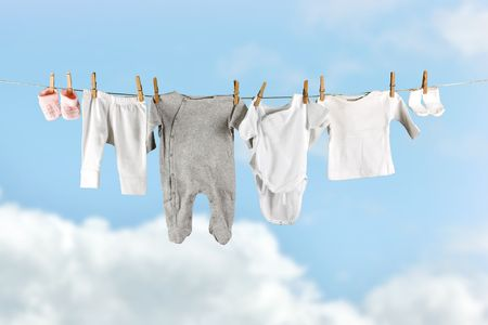 Baby laundry hanging in the sky on a clothesline photo