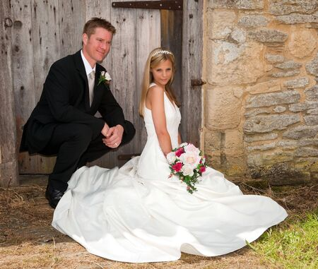 Young wedding couple against a grunge medieval wall Stock Photo - 6431321