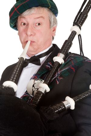 bagpipes: Scottish highlander wearing kilt and playing bagpipes Stock Photo
