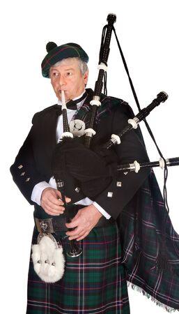 Scottish highlander wearing kilt and playing bagpipes photo