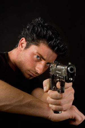 firearm: Young man aiming and firing a deadly weapon