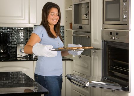 baking oven: Young women taking fresh baked cookies out of the oven Stock Photo