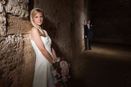 Bride in white posing against a medieval grunge barn wall Stock Photo - 6469237
