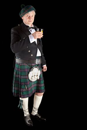 Scotsman in kilt making a toast with scottish whiskey photo