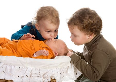 the three sisters: Toddler children admiring their newborn little sister