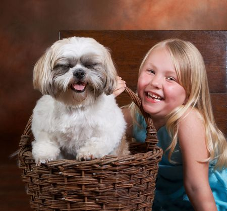 Little blond girl and her dog, both with a big smile photo