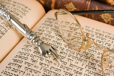 shabbat: Silver Torah pointer lying on a jewish prayer book Stock Photo
