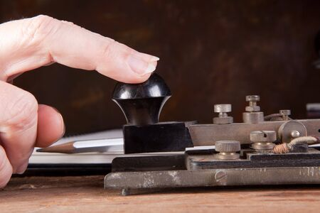 telegraaf: Vingers tikken morse code op een antieke telegraaf