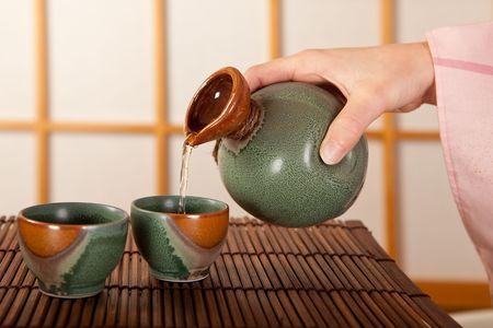 日本酒: 女性の手日本の酒を注ぐ 2 杯