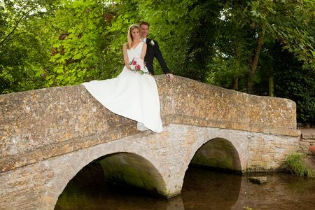 old packhorse bridge: Loving newly wed couple posing on a medieval grunge packhorse bridge