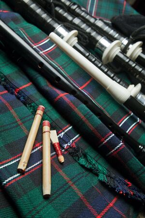 Authentic bagpipe reeds and bagpipes lying on a scottish tartan kilt photo