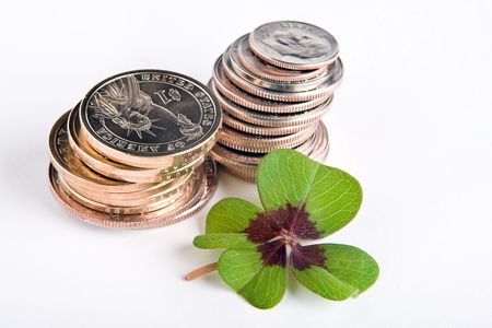 goodluck: Four-leaf clover on a stack of dollar coins Stock Photo