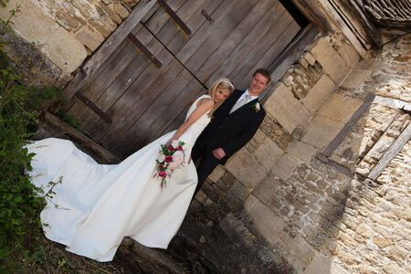 Young wedding couple against a grunge medieval wall photo