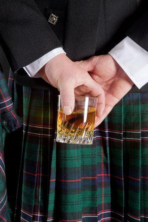 highlander: Escoc�s que mantiene su vaso de whisky detr�s de kilt  Foto de archivo