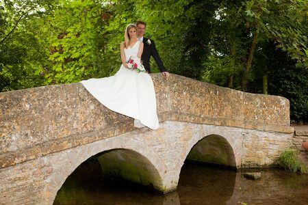Loving newly wed couple posing on a medieval grunge packhorse bridge photo