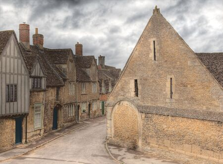 wiltshire: View on the medieval English cottages and tithe barn of 15th century Lacock village in Wiltshire