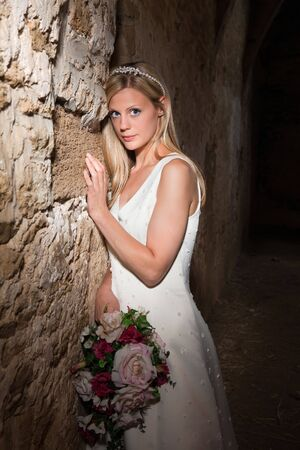 Bride in white posing against a medieval grunge barn wall photo