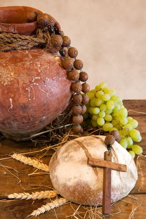 Antique wine jug, cross and rustic loaf of bread as christian symbols of faith photo