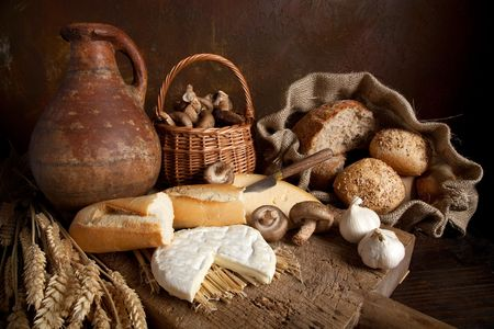 wine country: Country still life with bread, cheese, mushrooms and wine in an antique jar Stock Photo