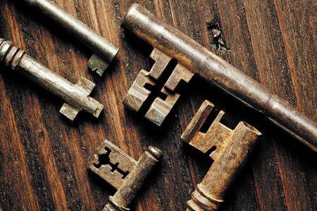 Grunge image of antique rusty keys on a weathered wooden background photo