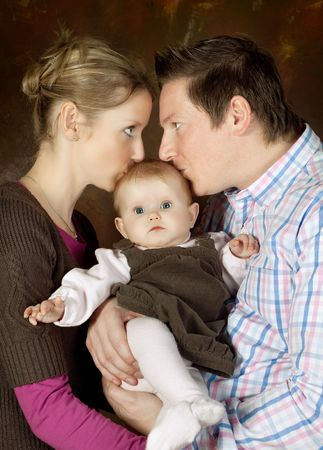 Happy mother and father kissing their 4 months old baby photo