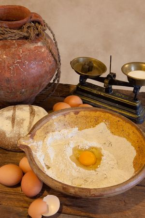 Flour and egg yolk in an antique bowl ready to make bread dough Stock Photo - 6700282