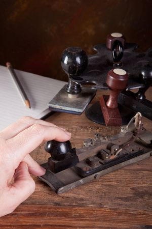 tapping: Hand tapping morse code on an antique telegraph machine