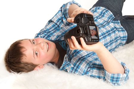 Boy with digital camera lying down and taking a self-portrait photo