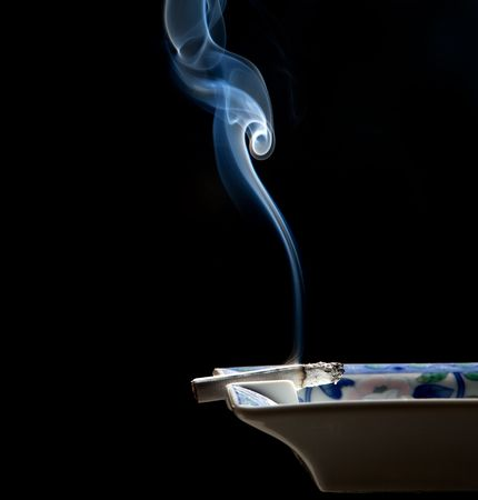 ashtray: Cigarette on ashtray with a beautiful wisp of smoke