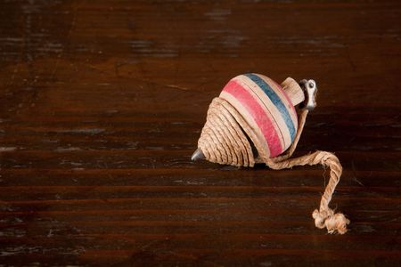 Antique spinning top on a brown wooden background